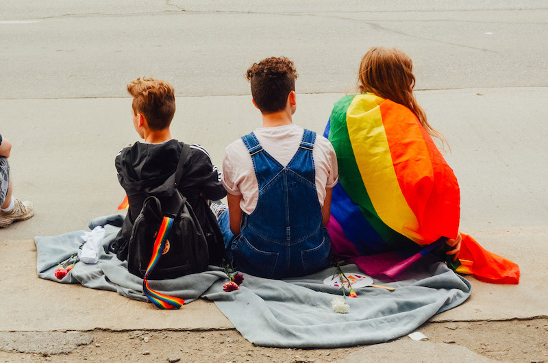 three kids seating on the floor holding a pride flag