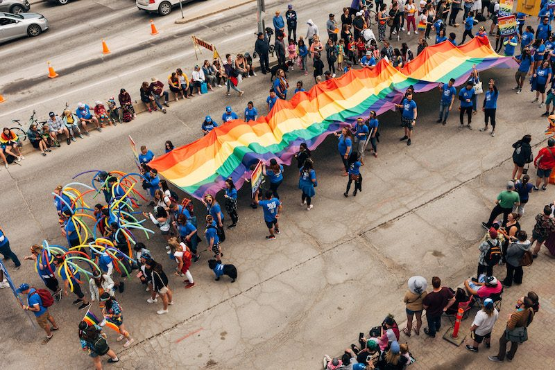 giant pride flag being hold during pride parade
