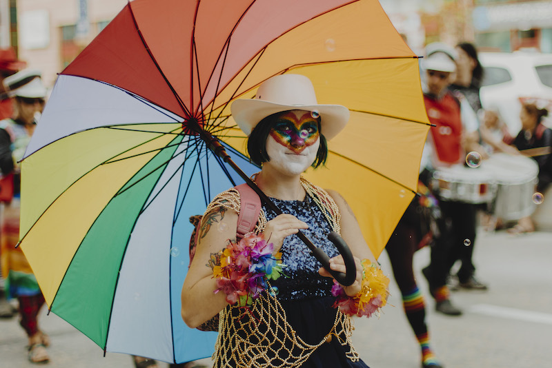 person parading in pride costume holding an umbrella