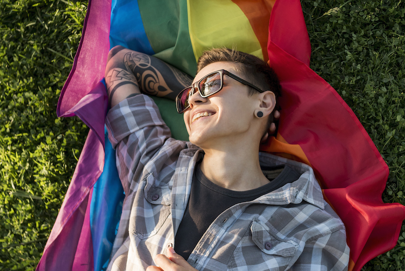 person laying on grass over pride flag